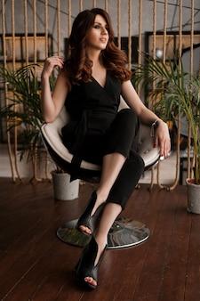 Портрет привлекательной женщины на удобном кресле для отдыха на чердаке с зелеными растениями