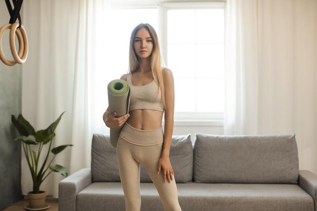 Портрет привлекательной женщины в спортивной одежде, держащей коврик для йоги или фитнеса после тренировки дома.