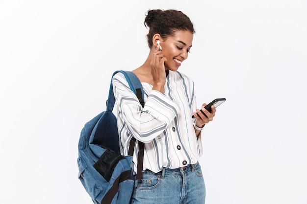 白い壁の上に孤立して立って、ワイヤレスイヤホンで音楽を聴き、携帯電話を持ってバックパックを運ぶ魅力的な若いアフリカの女性の肖像画