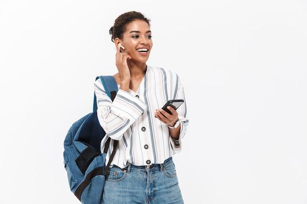 흰 벽에 격리된 채 배낭을 메고 무선 이어폰으로 음악을 들으며 휴대폰을 들고 있는 매력적인 젊은 아프리카 여성의 초상화