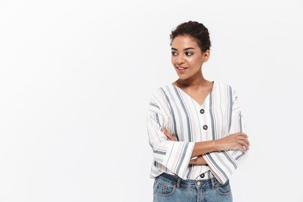 Портрет привлекательной молодой африканской женщины, стоящей изолированно над белой стеной, глядя в сторону