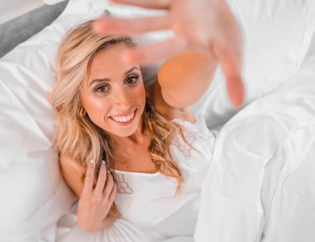 카메라에 그녀의 손을 넣어 침대에 잠옷에 매력적인 젊은 금발 백인 여자의 초상화