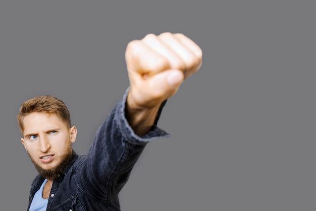 Портрет привлекательного молодого белокурого мужчины, смотрящего вверх кулаком, как супергероя, изолированного на сером фоне.