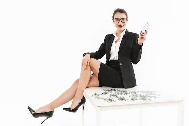 Портрет привлекательной молодой бизнес-леди в формальной одежде, сидящей на столе, изолированном над белой стеной, разговаривает по мобильному телефону