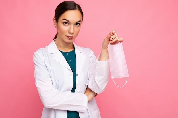 ピンクの壁に隔離されて立っている医療マスクを保持している白いコートの魅力的な若い女性医師の肖像画。