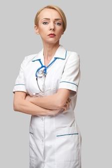 明るい灰色の背景に白衣を着た魅力的な若い女性医師の看護師の肖像画