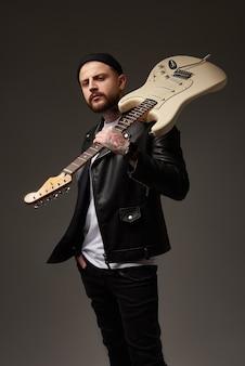 革のジャケットと彼の肩にエレキギターの入れ墨の魅力的な若い男の肖像暗い背景