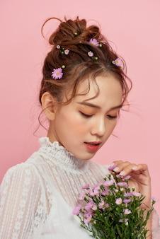 Портрет привлекательной молодой женщины, держащей букет и смотрящей через плечо, изолированной над розовым