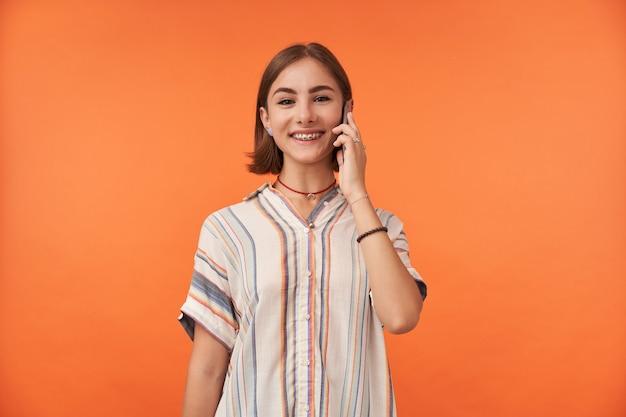 웃 고있는 매력적인 젊은 여자의 초상화입니다. 줄무늬 셔츠, 치아 교정기 및 팔찌를 착용하고 스마트 폰으로 대화하십시오. 고립 된 오렌지 벽 위에 서 서