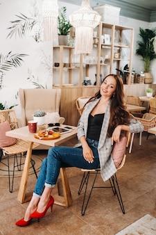 カフェに座っている魅力的な若い女性の肖像画