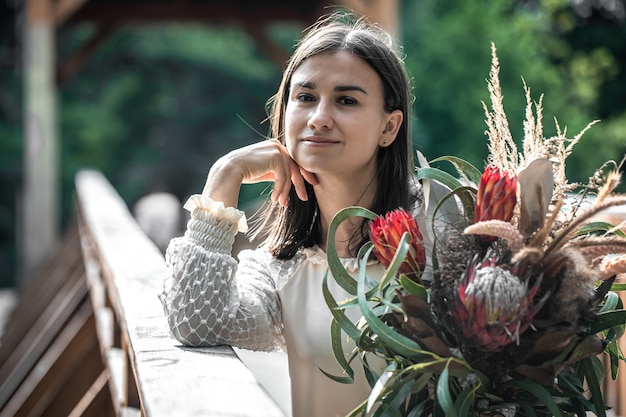 エキゾチックな花の花束、プロテアの花の花束を持つ魅力的な若い女性の肖像画。