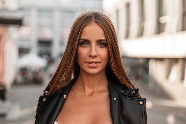 セクシーな唇と茶色の髪の美しい青い目を持つ魅力的な若い女性の肖像画。ファッショナブルな革のジャケットを着たかなり魅力的な女の子のモデルは、晴れた秋の日に街を歩きます。
