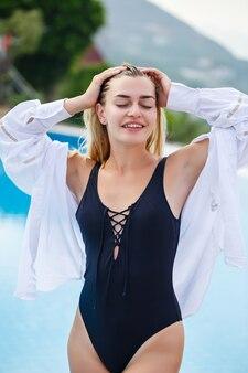 黒の水着と白いシャツのブロンドの髪を持つ魅力的な若い女性の肖像画