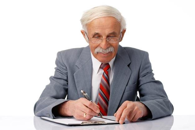 白の上にドキュメントに何かを書いている年配のビジネスマンの肖像画。