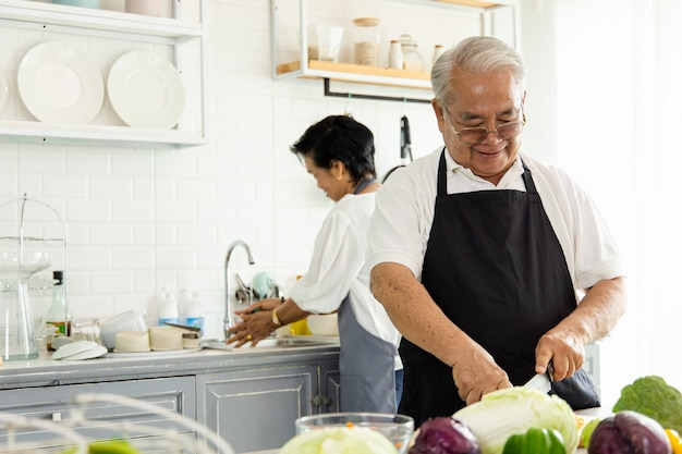 Портрет пожилой азиатской пары, готовящей на домашней кухне. у них улыбающееся лицо, и они довольны занятиями.