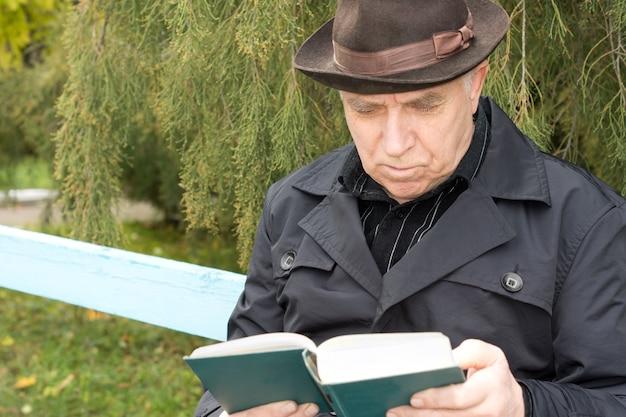屋外で読書をしている木製の公園のベンチに座っているオーバーコートと帽子をかぶった年配の紳士の肖像画