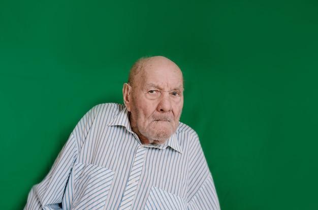 Портрет пожилого мужчины на зеленом фоне