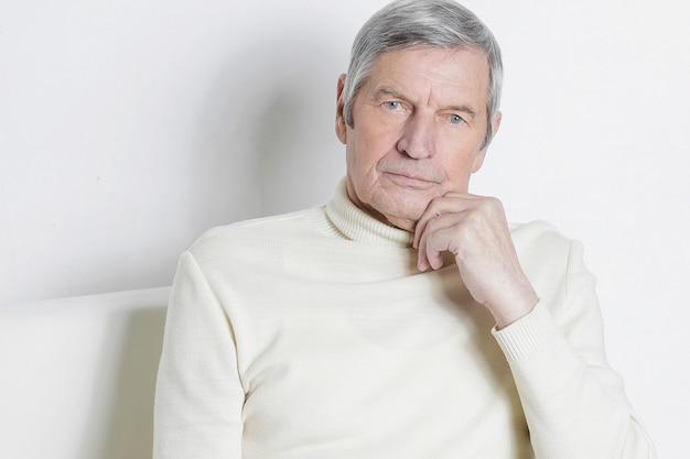 椅子に座っている老人の肖像画。白い壁に隔離
