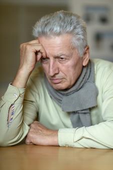 Портрет пожилого мужчины с головной болью на бежевом фоне