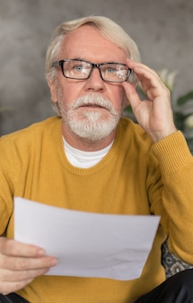 クレジット手形または公共料金の請求書を保持しているカメラを見ている白髪とひげを持つ老人の肖像画