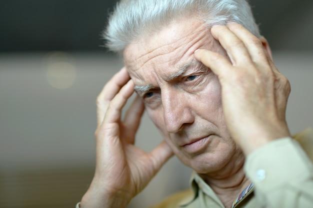 Портрет пожилого мужчины с головной болью