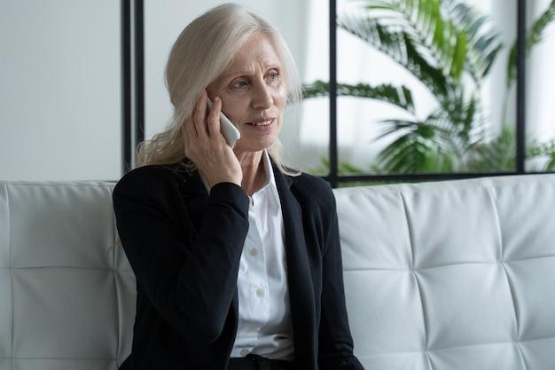 Портрет пожилой женщины в деловом костюме, сидящей на диване и с улыбкой разговаривающей по телефону. пожилая женщина разговаривает по мобильному телефону. концепция общения и выхода на пенсию.
