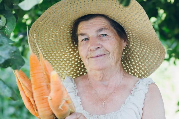 ニンジンを保持している帽子の高齢者の女性の肖像画