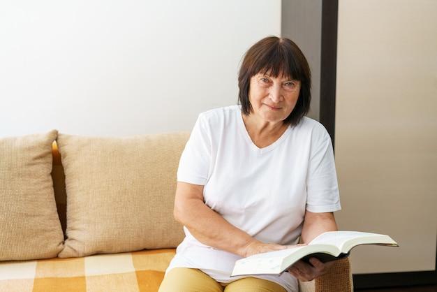 自宅のソファで本を読んでいる年配の女性の肖像画白人年金受給者は彼女の自由な時間を過ごします...