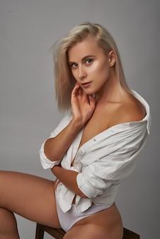 사려 깊은 흰색 배경을 찾고 스튜디오에서 흰색 란제리와 셔츠를 입고 금발 머리를 가진 우아하고 섹시한 여성 모델의 초상화