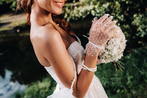 自然公園の自然の中で花束と白いドレスを着たエレガントな花嫁の肖像画。ウェディングドレスと手袋のモデルと花束。ベララス。