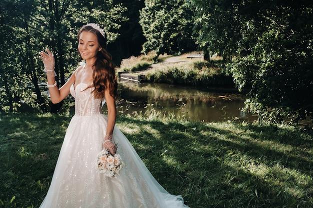 自然公園の自然の中で花束と白いドレスを着たエレガントな花嫁の肖像画。結婚式のドレスと手袋と花束のモデル。ベララス