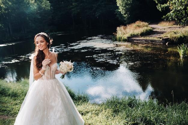 Портрет элегантной невесты в белом платье с букетом на природе в природном парке.