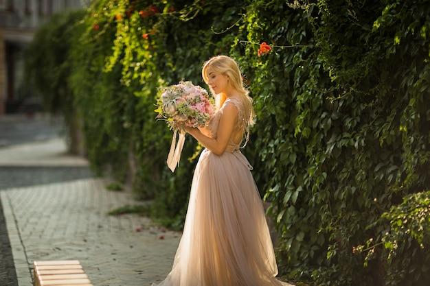회색 웨딩 드레스를 입고 거리에서 포즈를 취하는 우아한 예쁜 여성의 초상화. 신부는 파스텔 꽃과 녹지의 꽃다발을 들고