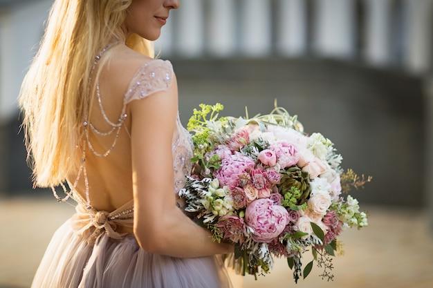 회색 웨딩 드레스를 입고 거리에서 포즈를 취하는 우아한 알아볼 수 없는 예쁜 여성의 초상화. 신부는 파스텔 꽃과 녹지의 꽃다발을 들고