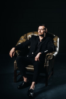 Портрет элегантного молодого европейца в костюме, сидящем на стуле в темном интерьере.