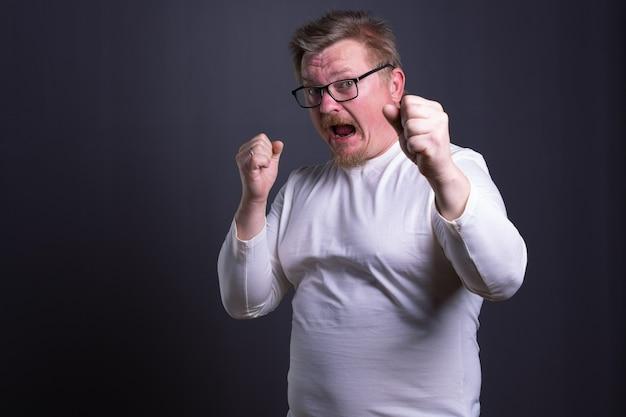 싸움을 위해 주먹을 쥔 회색 배경에 안경을 쓴 감정적인 남자의 초상화