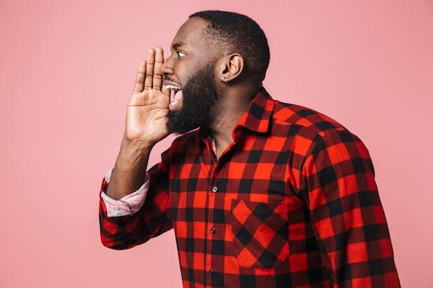 ピンクの壁の上に孤立して立って、叫び、目をそらしている格子縞のシャツを着て興奮しているアフリカ人の肖像画