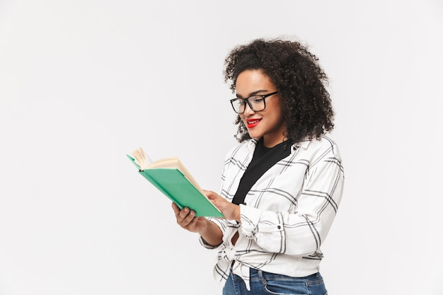 Портрет возбужденной африканской женщины, стоящей изолированно на белом фоне и читающей книгу