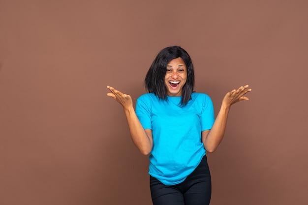 Портрет возбужденной и счастливой красивой молодой африканской женщины, смотрящей прямо в камеру, стоящей на простом фоне