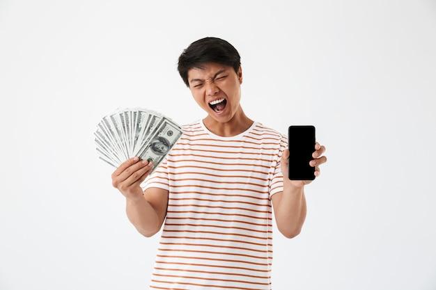 Портрет возбужденного азиатского мужчины, держащего деньги