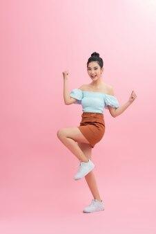 ピンクの背景に分離されたカメラをジャンプして見て興奮しているアジアの女性の肖像画