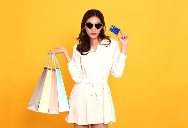 白いドレスと黄色の壁に分離された買い物袋を保持しているクレジットカードを着て興奮している美しいアジアの女性の肖像画。 Premium写真