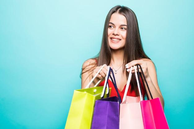 赤いドレスと青い壁に隔離の買い物袋を保持しているサングラスを身に着けている興奮した美しい少女の肖像画