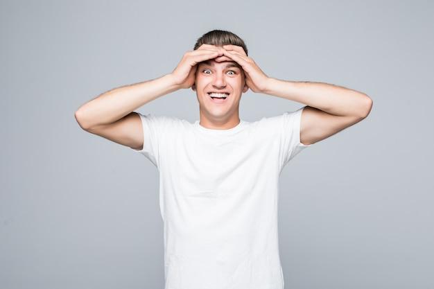 Портрет возбужденного мальчика-мужчины, держащего руки на голове, изолированного на белом