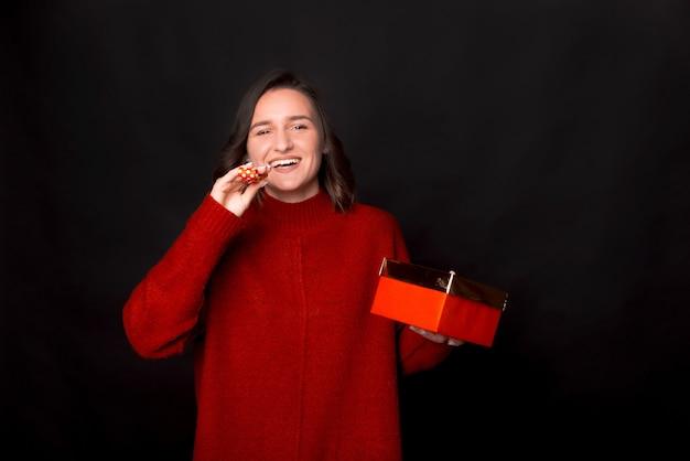 선물 상자를 들고 빨간 스웨터에 흥분된 귀여운 여자의 초상화