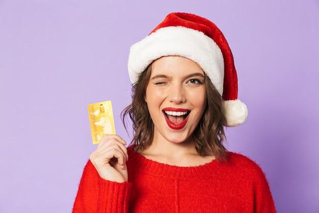 Портрет возбужденной счастливой молодой женщины в рождественской шляпе, изолированной над фиолетовой стеной, держащей подмигивающую дебетовую карту.