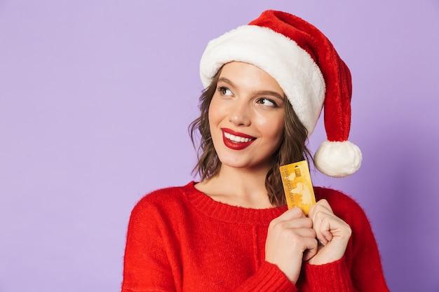 Портрет возбужденной счастливой молодой женщины в шляпе рождества изолированной над фиолетовой стеной, держащей дебетовую карту.