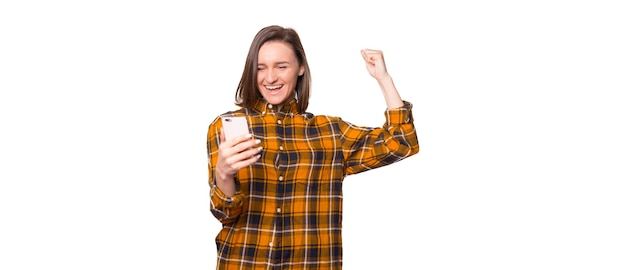Портрет возбужденной красивой девушки в клетчатой рубашке, смотрящей на мобильный