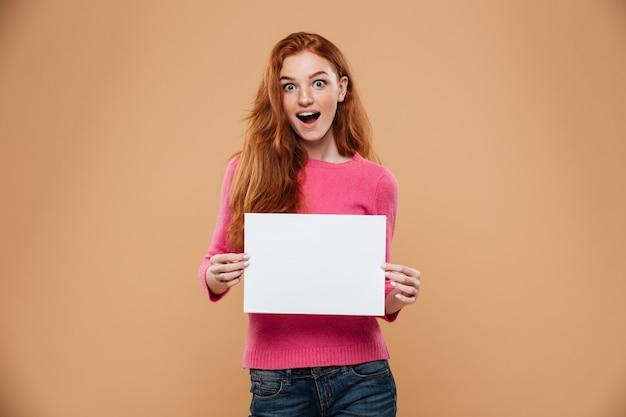 Портрет возбужденного довольно рыжая девушка держит пустой белый плакат