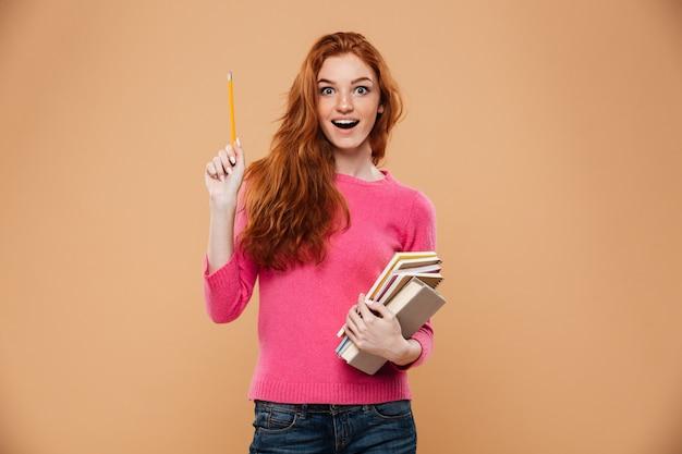 Портрет возбужденных довольно рыжая девушка держит книги и имея идею